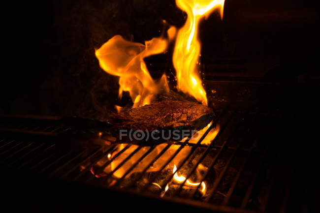 Close-up view of delicious steak cooking on grill with smoke and flame — Stockfoto