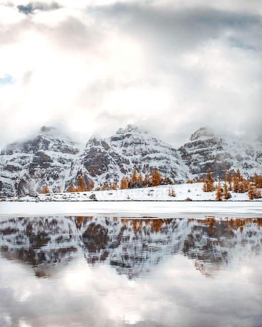 Schöne schneebedeckte Berge und Orangenbäume im ruhigen See an bewölktem Tag reflektiert — Stockfoto