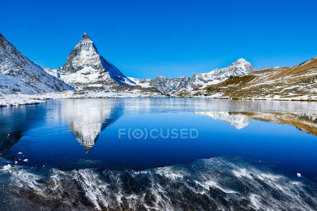 Beautiful snow-covered mountains reflected in calm lake at sunny day — стокове фото