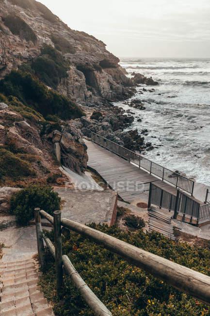 Escadas perto dos penhascos da montanha e da praia do oceano, opinião de ângulo elevado — Fotografia de Stock