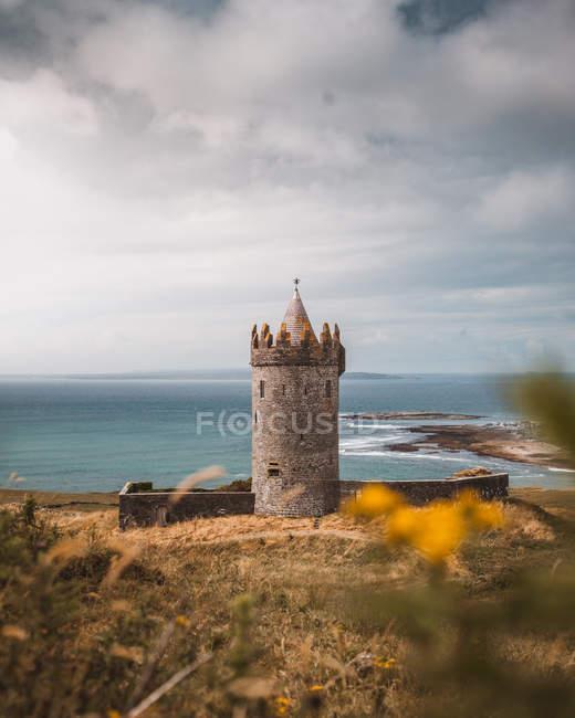 Foco seletivo do Castelo de pedra perto do corpo da água no dia nebuloso — Fotografia de Stock