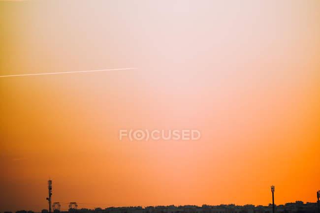 Streifen über goldenen Himmel über der Skyline der Stadt — Stockfoto