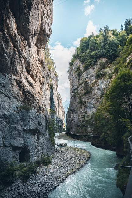 Scenic stream flowing by cliffs at sunny day — стокове фото