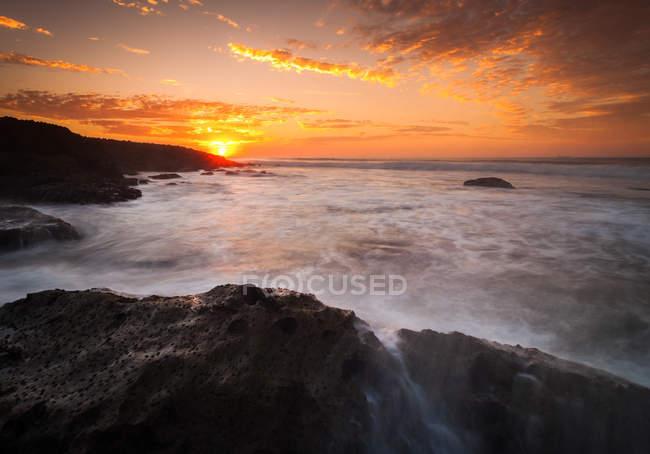 Удивительный вид на скалы и морские волны на красивом закате — стоковое фото