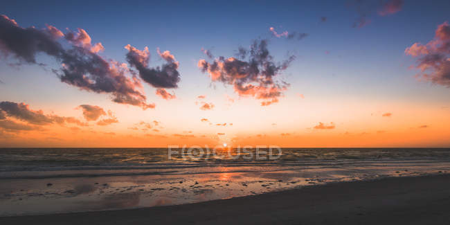 Sandy seashore, waves and clouds in sky during scenic sunrise — Foto stock