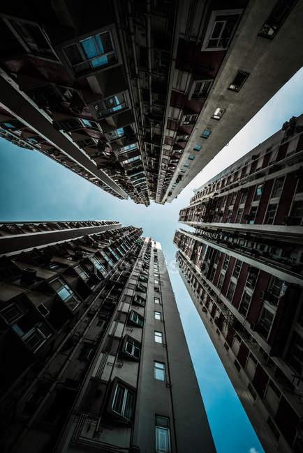Vista in basso di alti edifici moderni contro cielo azzurro chiaro — Foto stock