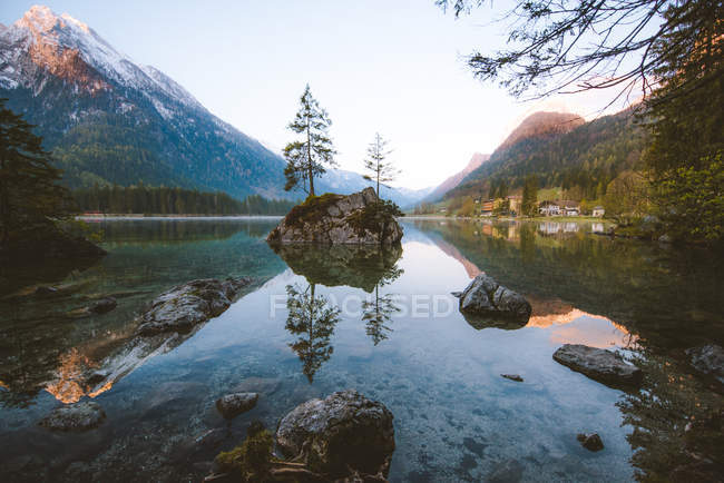 Beautiful mountains, rocks and green trees reflected in calm water — Stock Photo