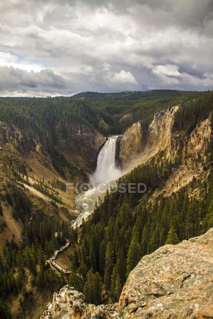 Aerial view of amazing waterfall in mountains under cloudy sky - foto de stock