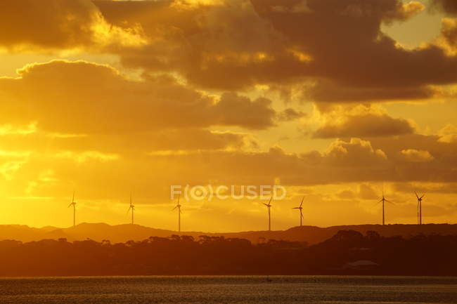 Silhouettes of windmills on hills and majestic sunrise — Foto stock