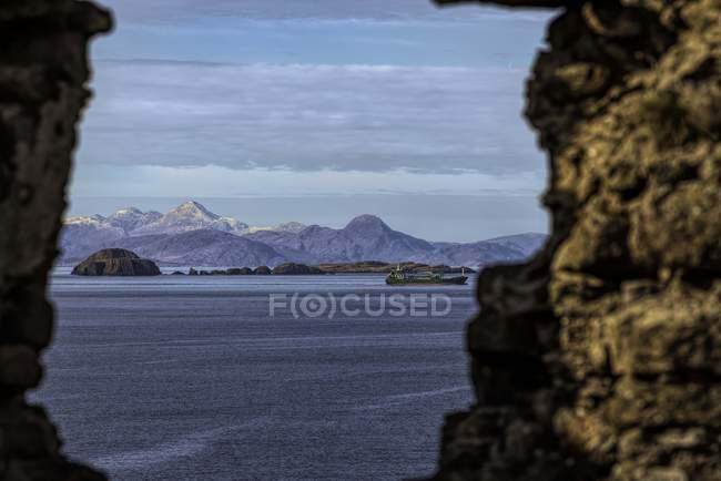 Mar calmo ao lado das pilhas e das montanhas na fotografia da natureza — Fotografia de Stock