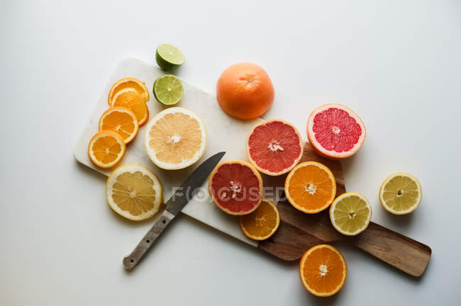 Top view of ripe sliced citrus fruits on cutting board on grey background — Stock Photo