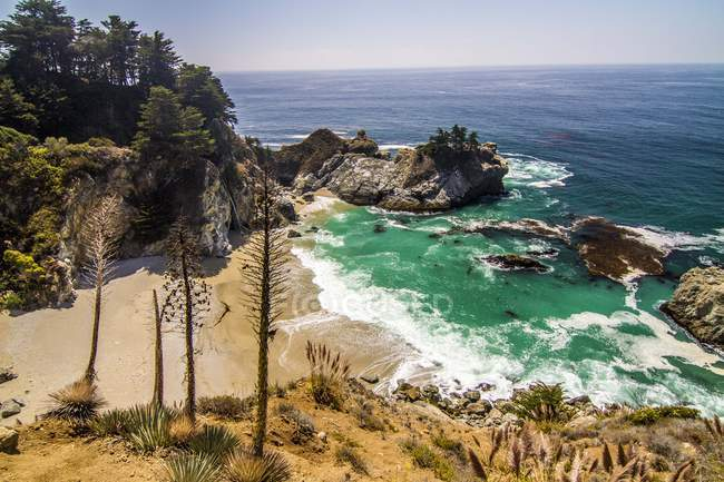 Aerial view of beautiful seascape, sandy beach and green trees on rocky mountains — стокове фото