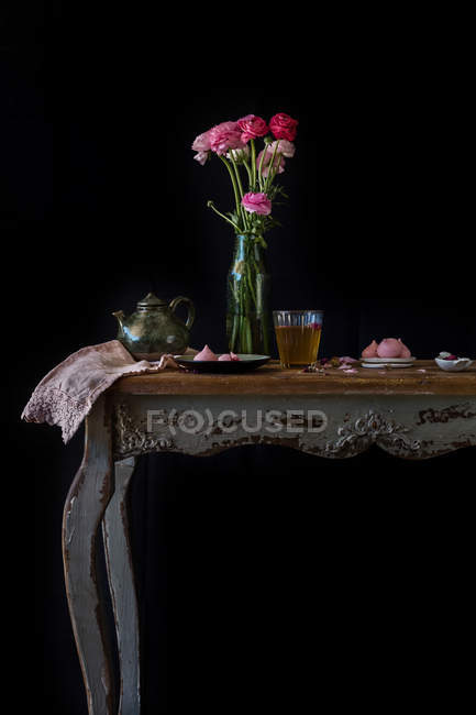 Still life with pink flowers in vase, glass, teapot and cookies on vintage table on black background - foto de stock