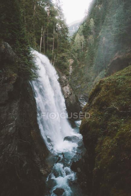Hermoso paisaje con cascada escénica, río rápido y montañas cubiertas de árboles verdes - foto de stock
