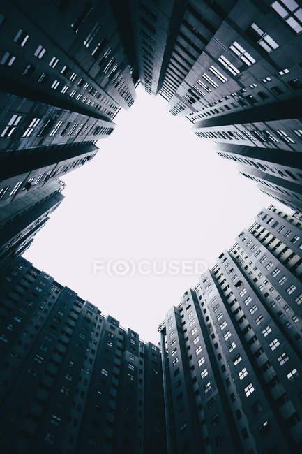 Vista in basso di edifici di cemento grigio contro cielo chiaro — Foto stock