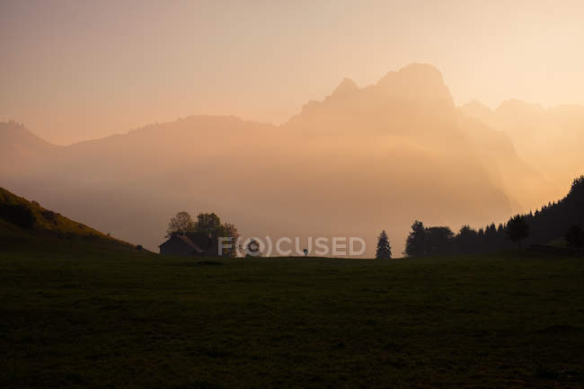 Beautiful green meadow and scenic mountains at sunrise — Stock Photo