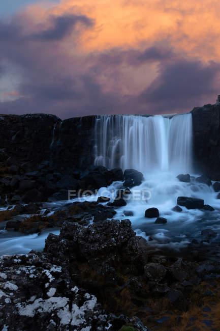 Дивовижний водоспад на скелях на мальовничому хмарний Схід сонця — стокове фото
