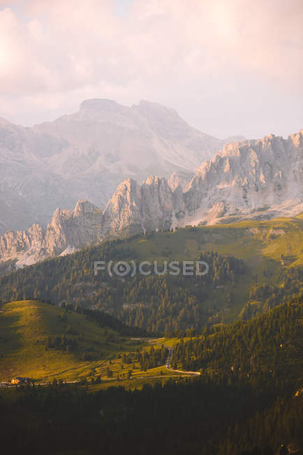 Aerial view of beautiful rocky mountains and scenic hills covered with green vegetation - foto de stock