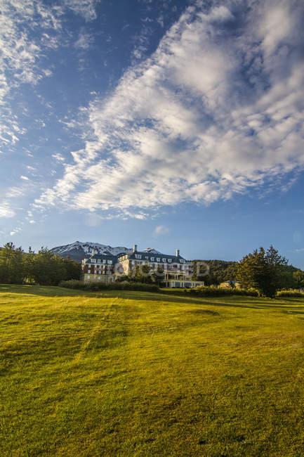 Отель на зеленой лужайке, деревьях и горах в солнечный день — стоковое фото