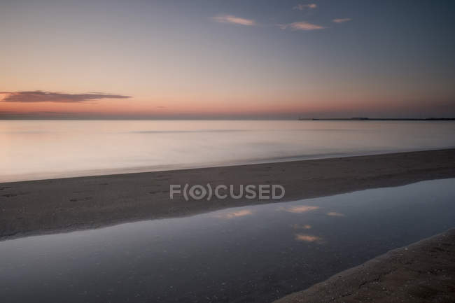 Sandy beach and sky reflected in water at sunset - foto de stock