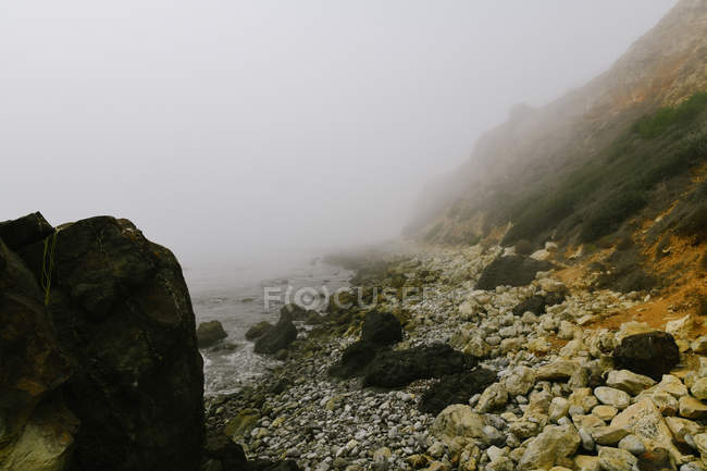 Beautiful rocky mountains and sea covered with mist — стоковое фото