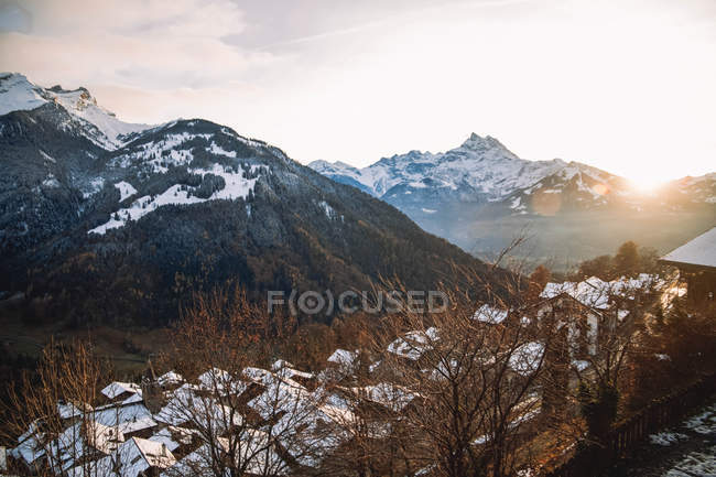 Beautiful scene with majestic mountains and village in valley at sunrise — Photo de stock