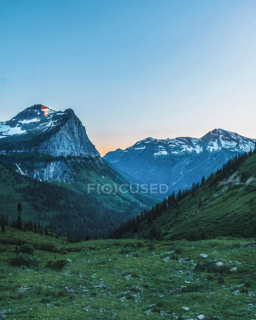 Majestic mountains with snow on peaks and green vegetation on hills - foto de stock
