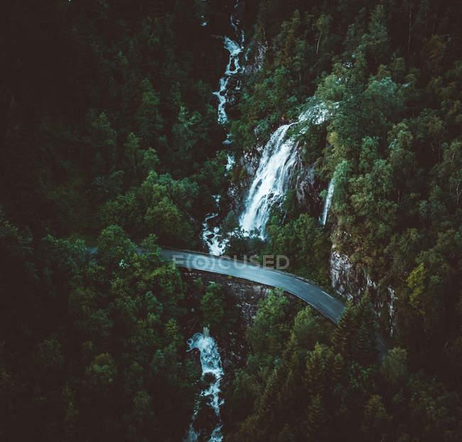 Vista aérea del puente estrecho escénico cerca de árboles verdes y majestuosas cascadas - foto de stock
