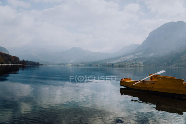 Beautiful natural view with mountains in mist and boat on calm lake — Stock Photo