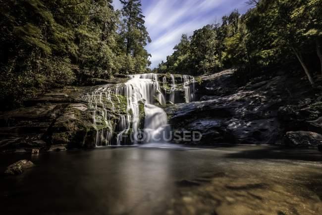 Красивий ландшафт з мальовничим водоспадом на скелях і зеленому лісі — стокове фото