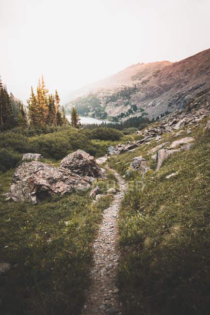 Caminho entre rochas em montanhas cénicas perto do lago — Fotografia de Stock