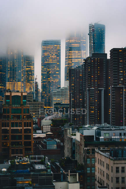 Amazing cityscape with tall illuminated buildings and skyscrapers at foggy evening — стоковое фото