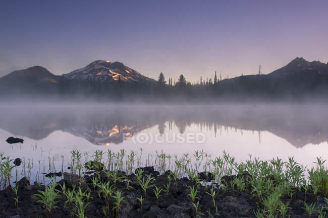 Herrliche natürliche Aussicht auf Nebel über ruhigen See und malerischen Bergen — Stockfoto