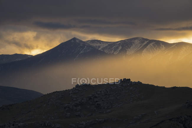 Amazing landscape with mountains and rocks under cloudy sky at sunset — Stock Photo