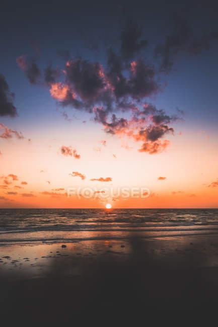 Vista surpreendente do mar e sol avermelhado no céu durante o por do sol — Fotografia de Stock