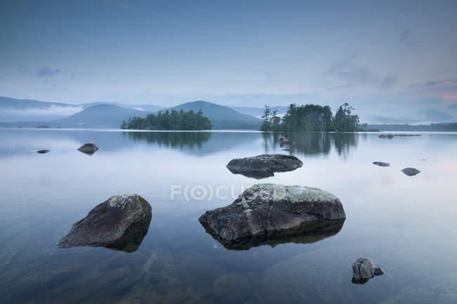 Vue naturelle étonnante avec des roches dans le lac calme et les montagnes à l'horizon — Photo de stock