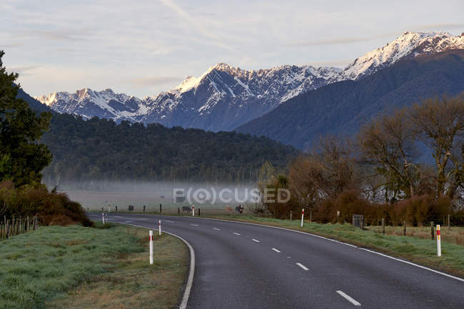 Bellissimo paesaggio con montagne innevate e strada asfaltata — Foto stock