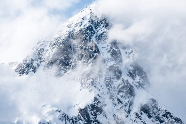 Beautiful landscape with snow-covered mountain in clouds — Stock Photo