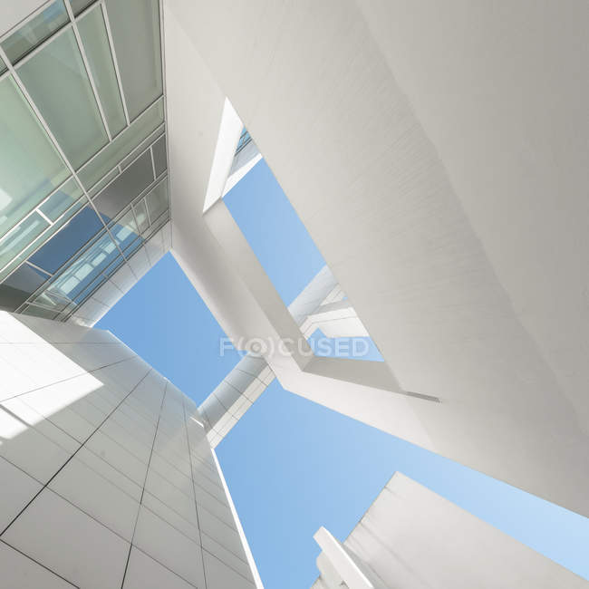 Низкий угол зрения высокого белого здания против голубого неба — стоковое фото