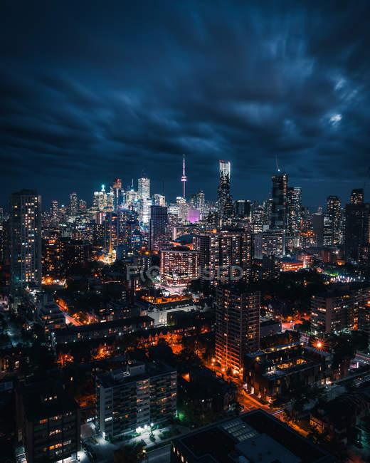 Vista aérea del increíble paisaje urbano con rascacielos iluminados por la noche - foto de stock
