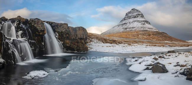 Vista cénico da cachoeira em rochas e na montanha coberta com a neve — Fotografia de Stock