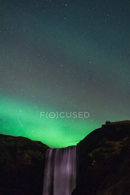 Majestic landscape with aurora borealis in sky over waterfall — Stock Photo
