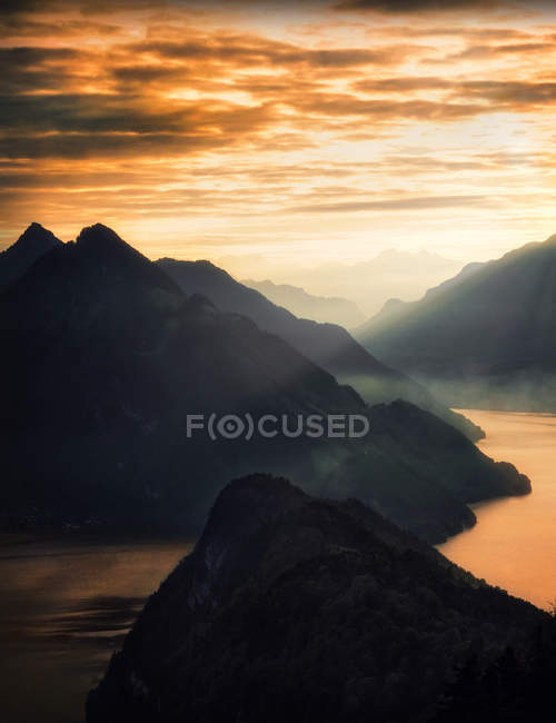 Amazing rocky mountains surrounding lake at cloudy sunrise - foto de stock
