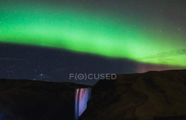 Majestic landscape with northern lights in sky over waterfall — Photo de stock