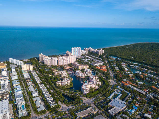 Aerial view of city with buildings, rooftops, green vegetation and calm blue sea — Fotografia de Stock