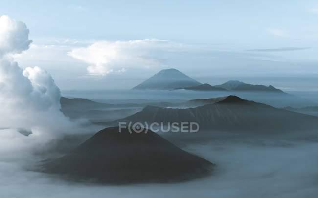 Vista aérea do vulcão surpreendente e das montanhas bonitas nas nuvens — Fotografia de Stock
