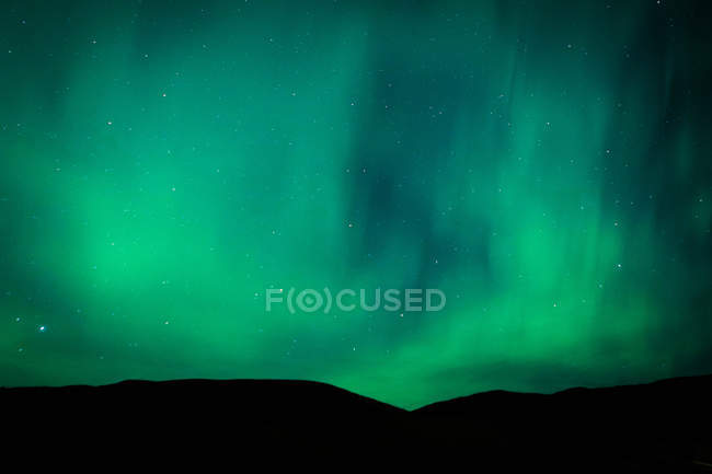 Erstaunliche natürliche Ansicht der Aurora borealis über dunklen Hügeln — Stockfoto