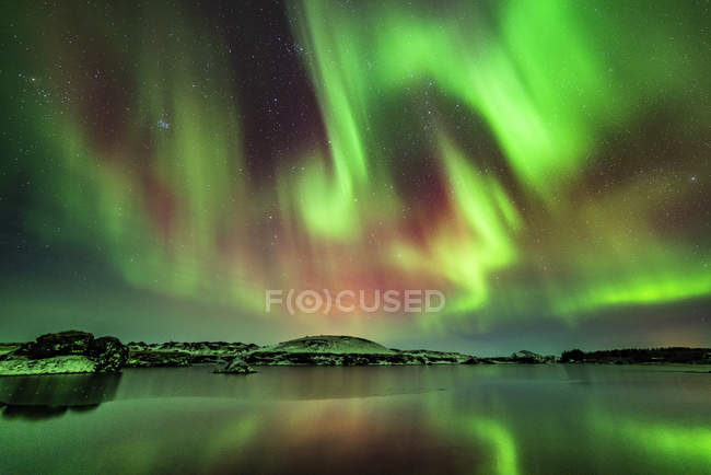 Amazing natural view of aurora borealis above body of water — Stock Photo