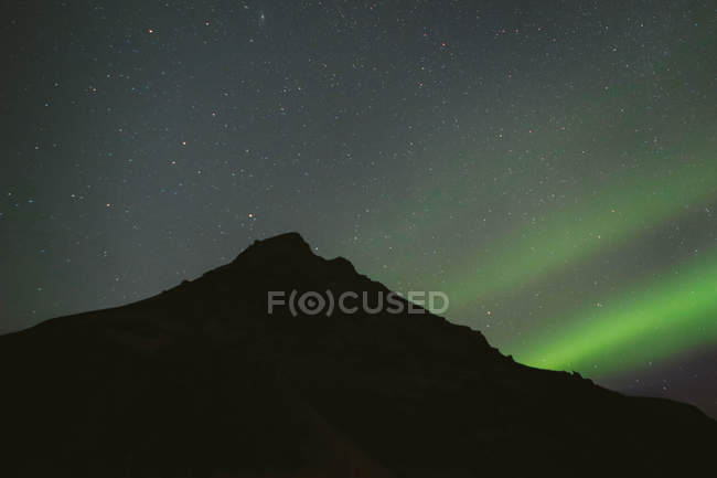 Black silhouette of mountain and Northern Lights in night sky — Stock Photo