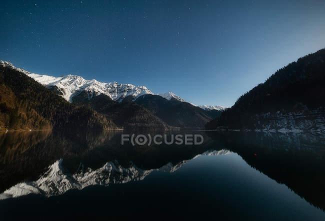 Incredibili montagne rocciose con neve sulle cime riflesse in un lago calmo — Foto stock